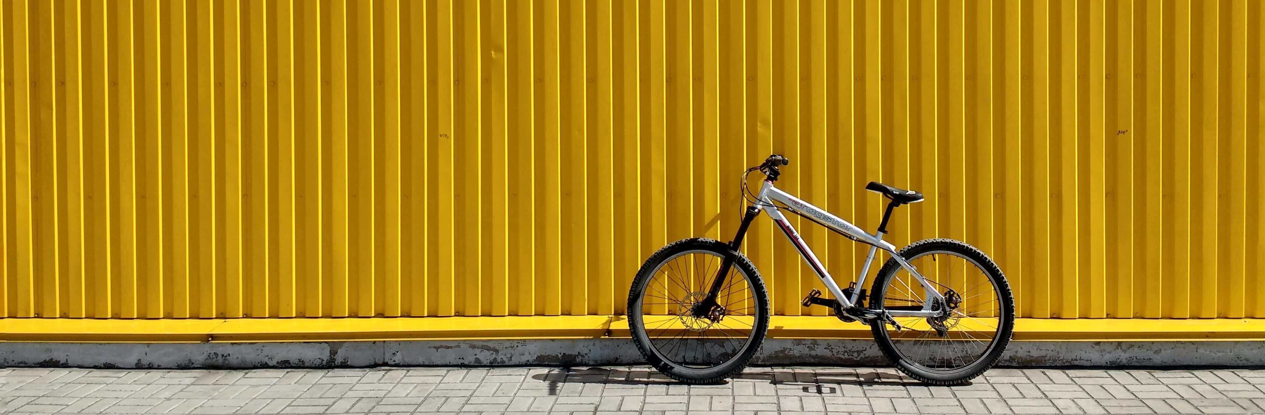 A bike leaning against a yellow wall, decorative image.